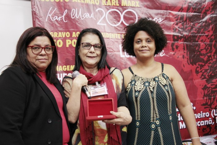 Jaqueline e Bianka entregam comenda à família de Mariele Franco, recebida pela feminista