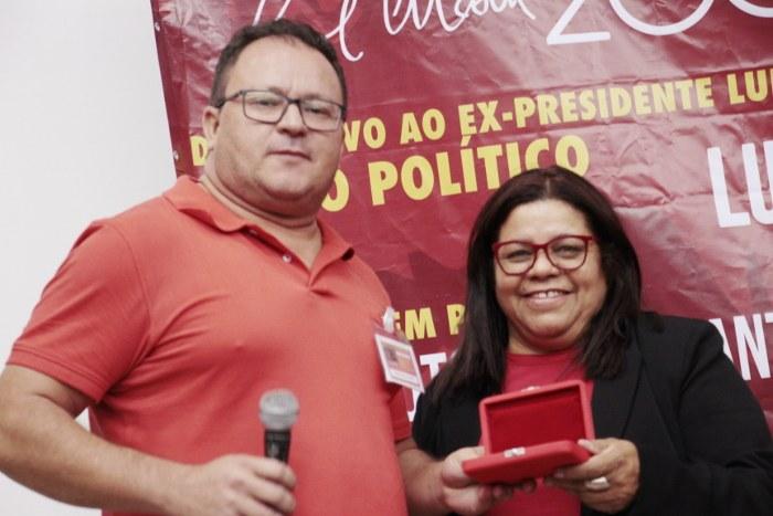 Prof. Adelmar (CLCN-GO) recebe de Jacqueline Alves a comenda Imprescindível a ser entregue a ........